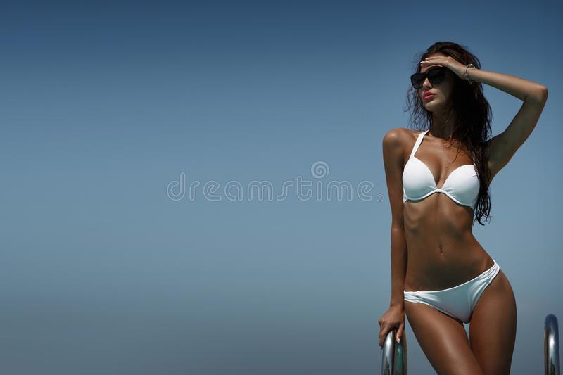 Elegant woman in the white bikini on the sun-tanned slim body is posing near the swimming pool in a good hot weather. Elegant young woman in the white bikini and stock photos