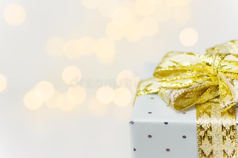 Elegant silver gift box tied with golden ribbon with bow bokeh garland lights on white background. Christmas New Years presents royalty free stock photo