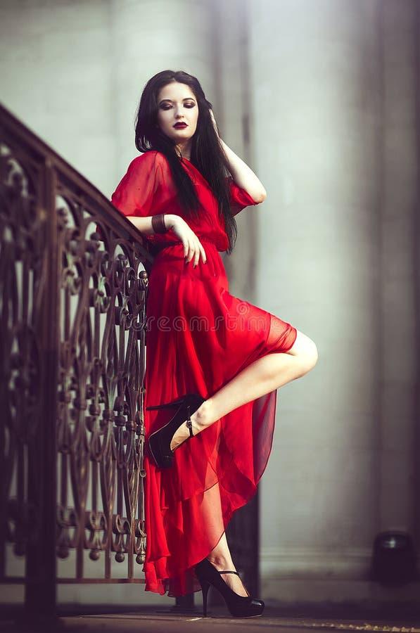 Elegant sinnlig sexig ung kvinna i den röda klänningen som poserar nära en ledstång fotografering för bildbyråer