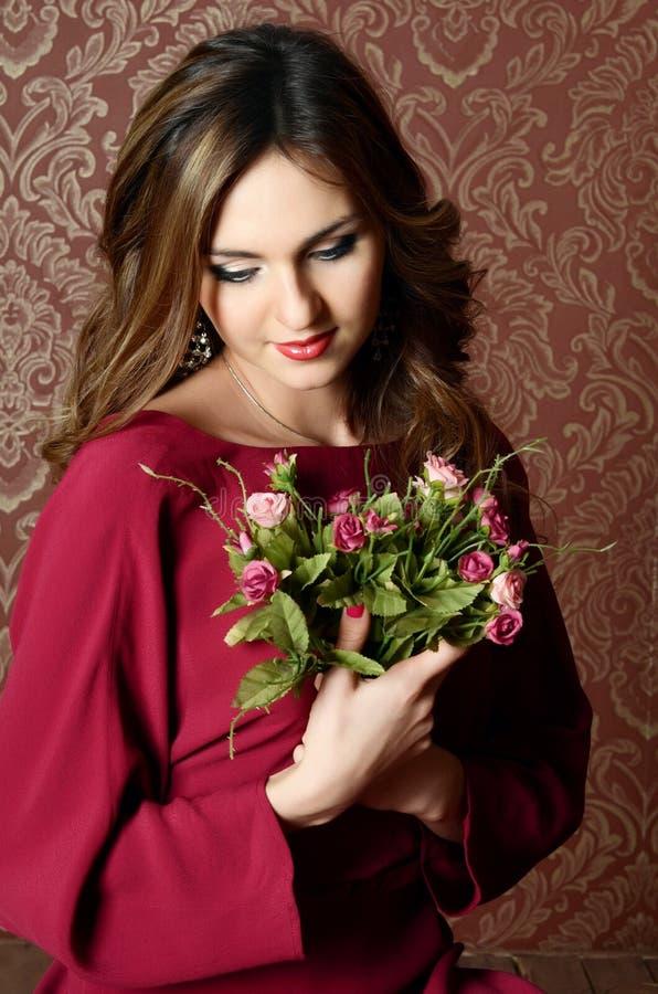 Den eleganta sinnliga unga kvinnan i en claretklänning arkivfoton