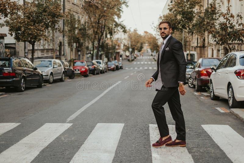 Elegant skäggig affärsman som korsar gatan royaltyfri foto