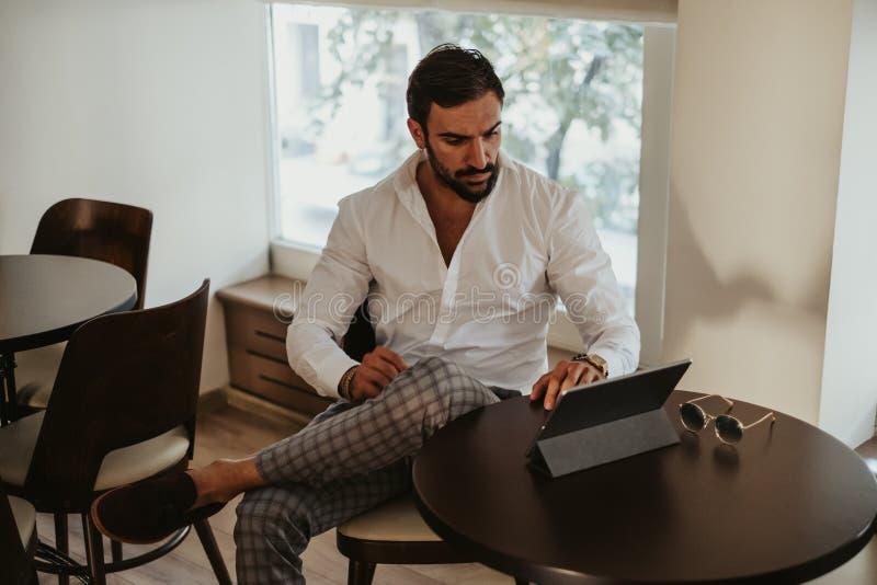 Elegant skäggig man som ser minnestavlan i ett kafé royaltyfri fotografi