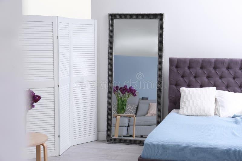 Elegant slaapkamerbinnenland met spiegel royalty-vrije stock afbeelding