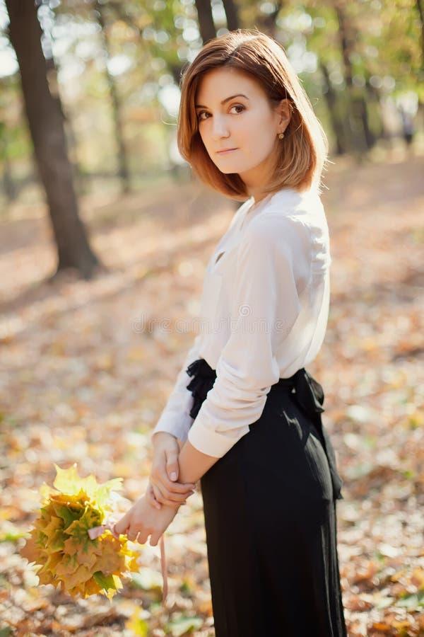 Elegant slank jong meisje in de herfstpark royalty-vrije stock afbeeldingen