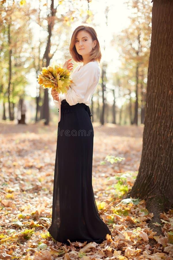 Elegant slank jong meisje in de herfstpark stock foto