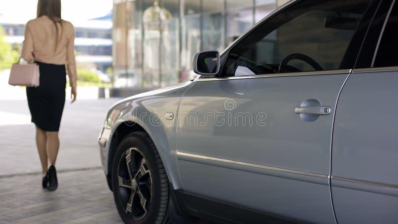 Elegant slank kvinna som går till affärsmitten, närliggande parkerad bil, tillbaka sikt arkivfoto