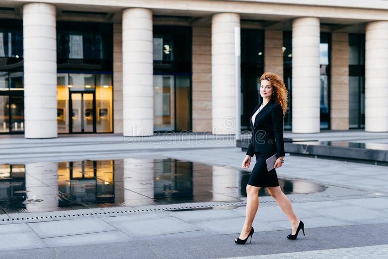 Elegant slim woman in black suit and high-heeled shoes, holding tablet in hands going for work. Businesswoman in motion. Confident stock image