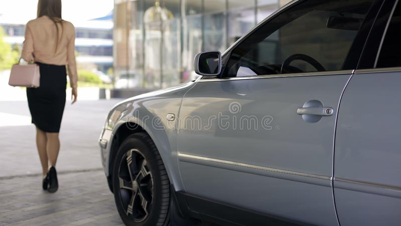 Elegant slim woman walking to business center, parked car nearby, back view stock photo