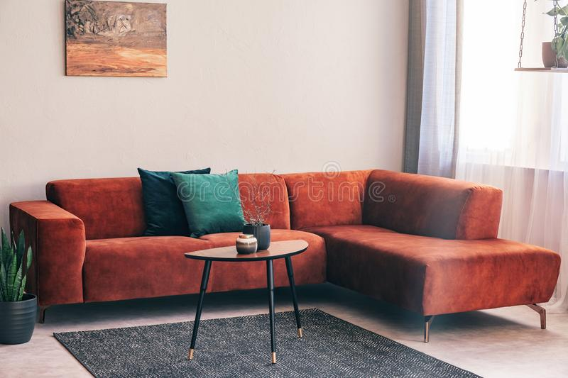 Elegant small wooden coffee table with lowers in front of big velvet corner sofa with pillows royalty free stock photos