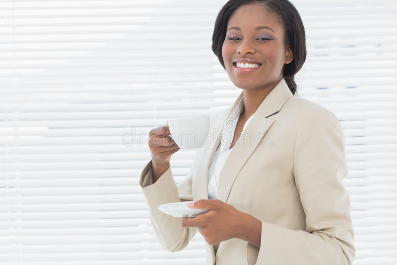Elegant smiling businesswoman with a cup of tea in office stock images