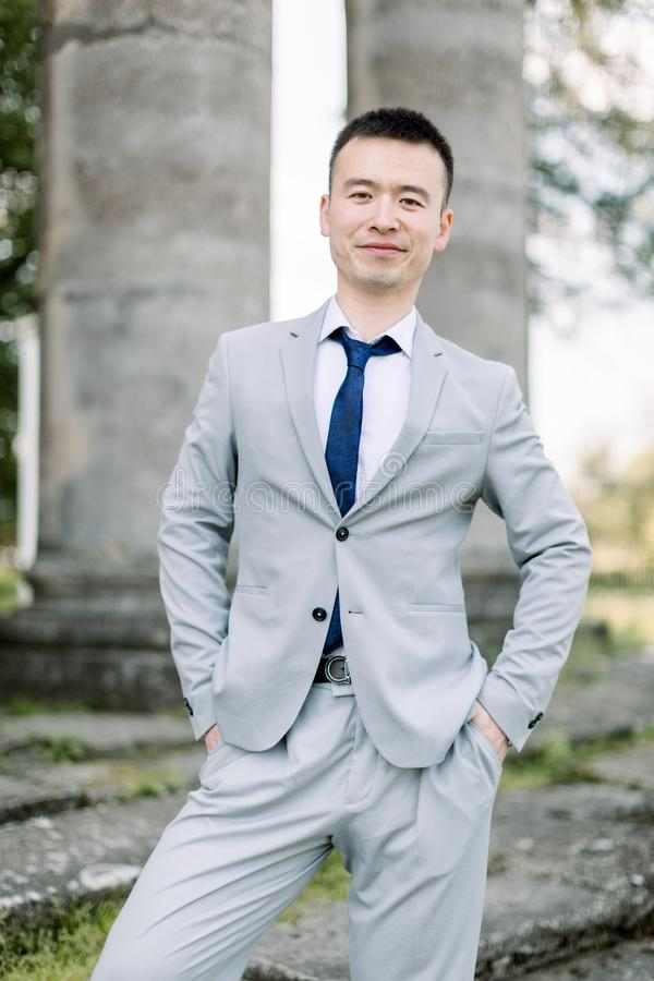 Elegant smiling handsome Asian groom in gray suit posing on the background of ancient stone columns in old castle royalty free stock photos