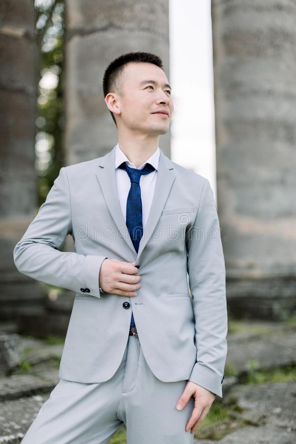 Elegant smiling handsome Asian groom in gray suit posing on the background of ancient stone columns in old castle royalty free stock photography