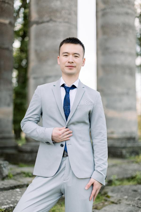 Elegant smiling handsome Asian groom in gray suit posing on the background of ancient stone columns in old castle stock image