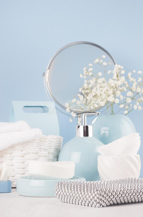 Elegant soft bathroom dressing table with products for body and skin care, white flowers, towels, mirror, ceramic blue vase. Elegant soft bathroom dressing stock photo