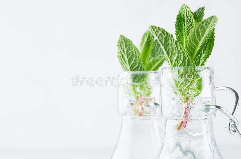 Elegant soft white summer background -young mint leaves closeup in transparent bottles with sparkling bubbles on light wood table. Elegant soft white summer royalty free stock photography