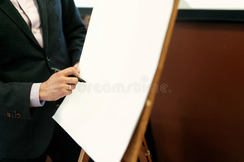elegant speaker lecturer hands holding marker and writing at empty white board at business meeting , marketing lecture royalty free stock images