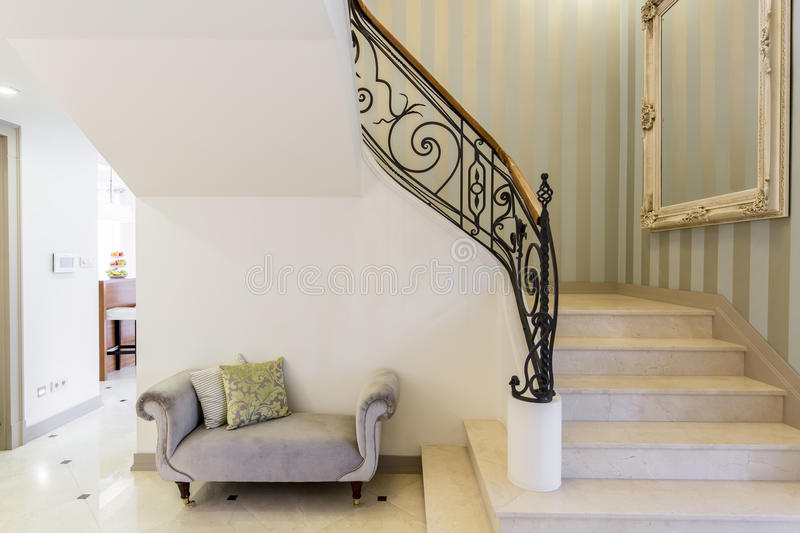 Elegant staircase with decorative railing. Big framed mirror and patterned couch stock photos