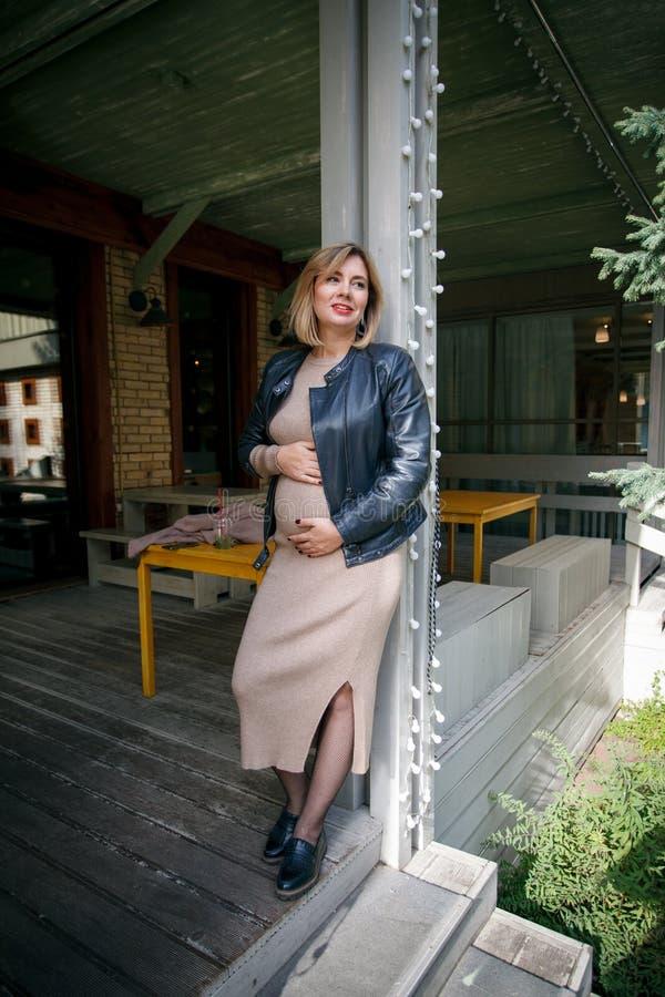 Elegant stil av en gravid kvinna i en modern stad Mode tenderar för gravida kvinnor royaltyfria foton
