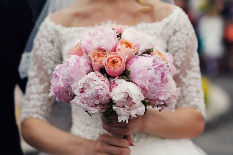 Elegant stilfull brud i tappningbröllopsklänning med rosa bouque royaltyfria bilder