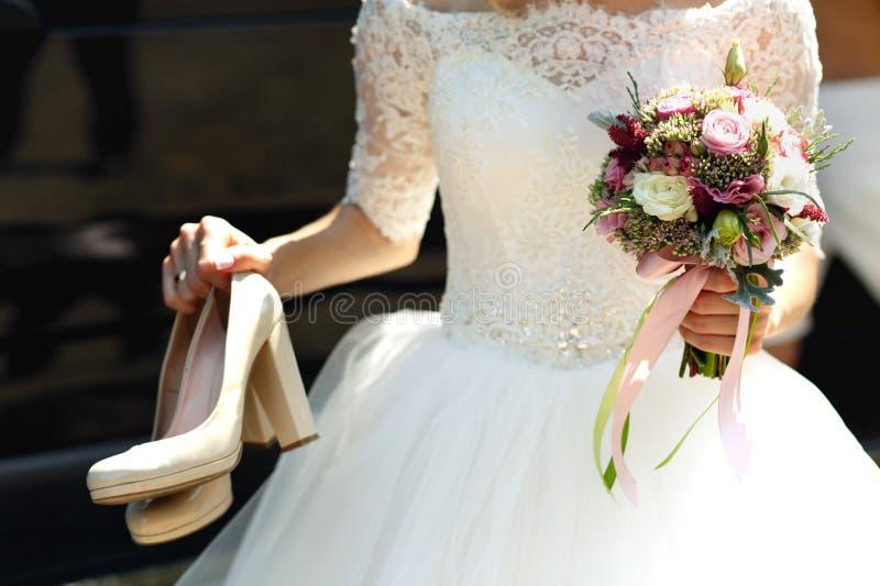 Elegant stilfull brud i vita tappningbröllopsklänningskor och b arkivbilder