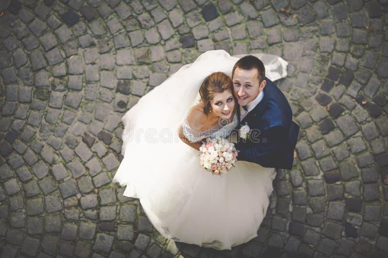 Elegant stilfull brudgum med hans lyckliga ursnygga brunettbrud på royaltyfri foto