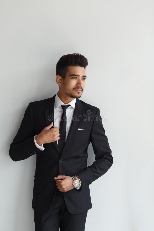 Elegant stilfull ung stilig man i en dräkt Manligt ta av ens kläder royaltyfri foto