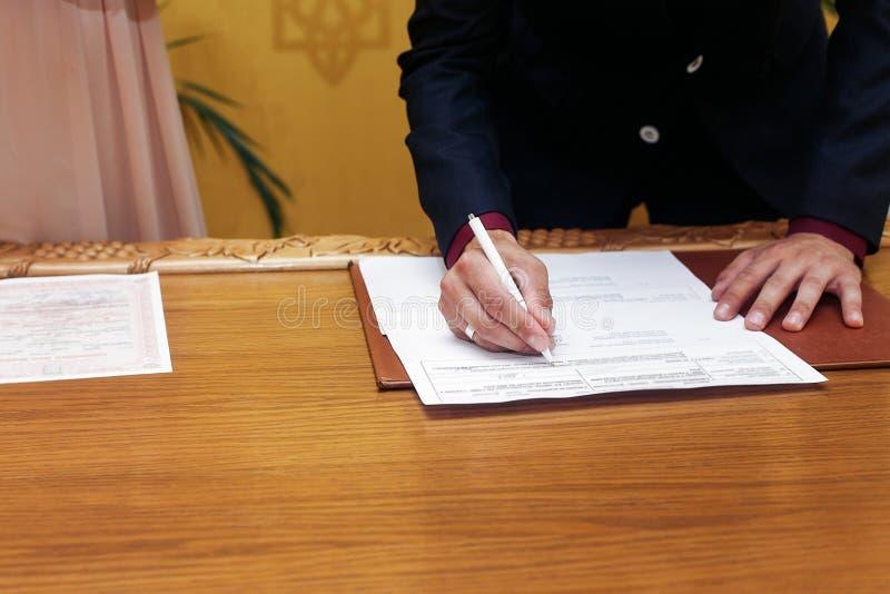 Elegant stilfullt brudgumunderteckningsregister, hållande penna och representant royaltyfri bild