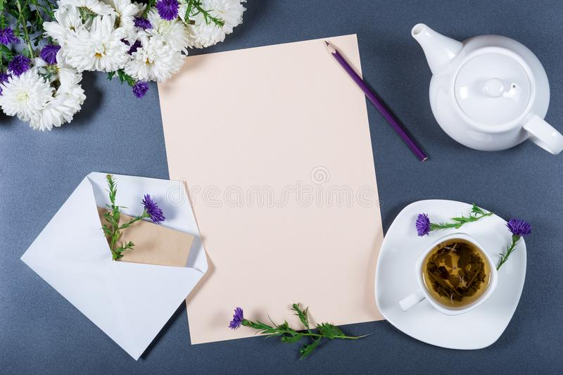 Elegant still life - sheet of paper, white and purple chrysanthemums, pencil, teapot, cup of herbal tea and envelope on gray desk royalty free stock photo