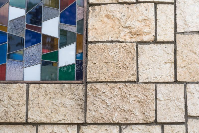 The stone wall is neatly tiled. The right corner is decorated with elements of multicolored mazaiki stock images