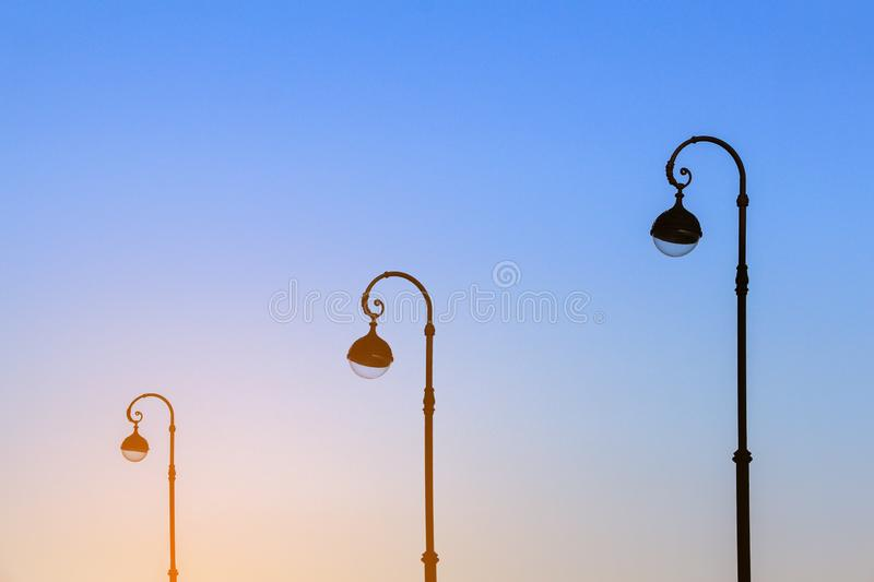 Elegant street lamps against the blue sky in the early morning in the light of the rising sun. Beautiful street lamps against the blue sky in the early morning royalty free stock photography