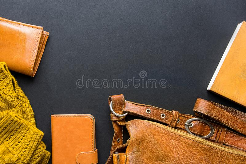 Elegant Stylish Female Women Accessories Yellow Leather Bag Wallet Knitted Sweater Notebook arranged in Flat Lay Composition. royalty free stock image
