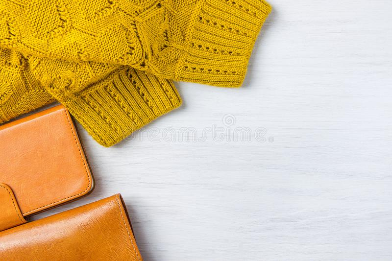 Elegant Stylish Female Women Accessories Yellow Leather Wallet Knitted Sweater Smartphone Case in Flat Lay Composition on White royalty free stock photos