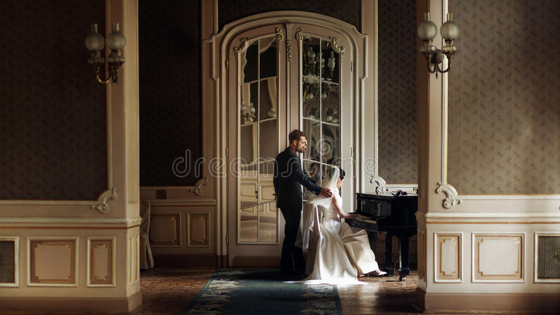 elegant stylish handsome groom looking at his gorgeous bride playing the piano. reflection in the mirror. unusual luxury wedding stock photo