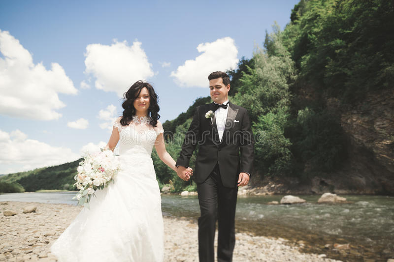 Elegant stylish happy brunette bride and gorgeous groom on the background of a beautiful waterfall in the mountains.  royalty free stock photo