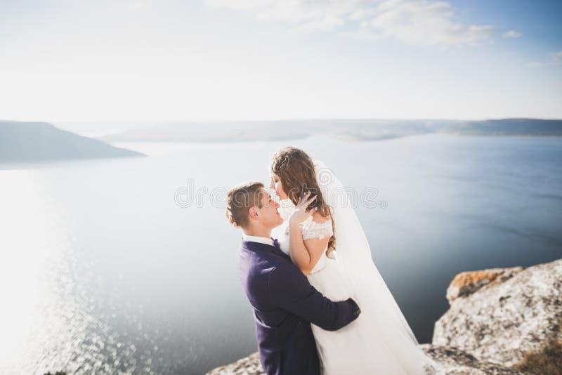 Elegant stylish happy wedding couple, bride, gorgeous groom on the background of sea and sky.  stock photography