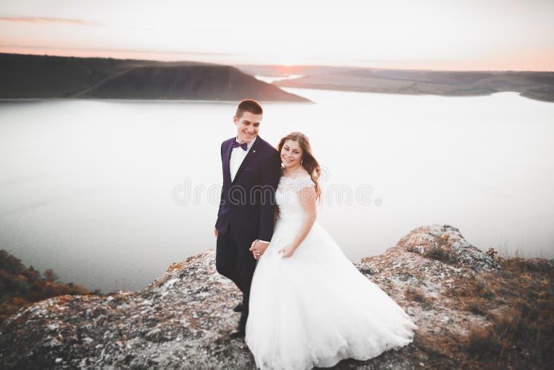 Elegant stylish happy wedding couple, bride, gorgeous groom on the background of sea and sky.  stock images