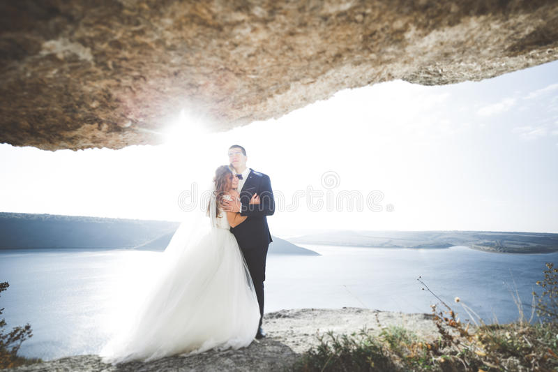 Elegant stylish happy wedding couple, bride, gorgeous groom on the background of sea and sky.  royalty free stock images