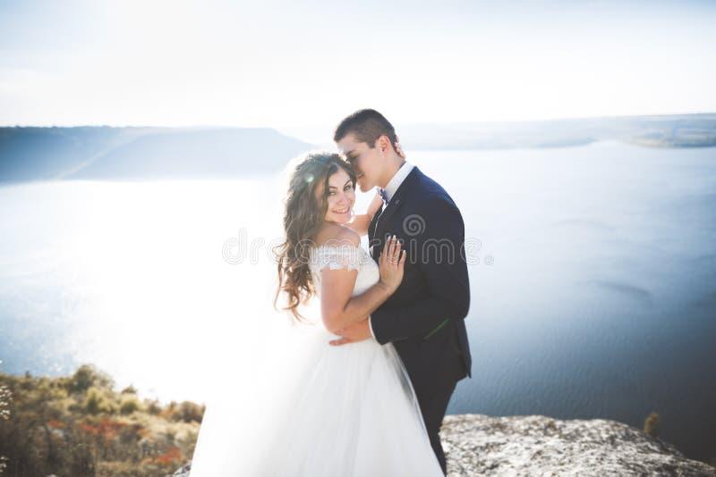 Elegant stylish happy wedding couple, bride, gorgeous groom on the background of sea and sky.  royalty free stock image