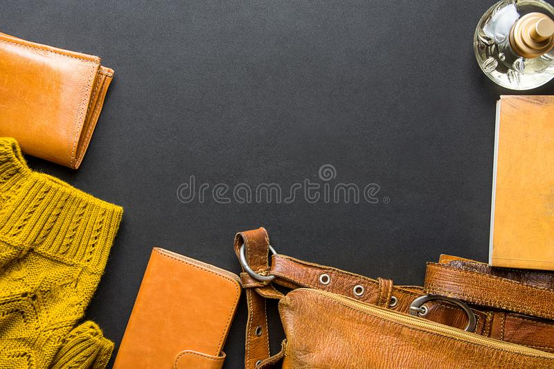 Elegant Stylish Luxury Female Women Accessories Yellow Leather Bag Wallet Knitted Sweater Perfume Notebook Flat Lay Still Life. Black Background. Fall Autumn stock image