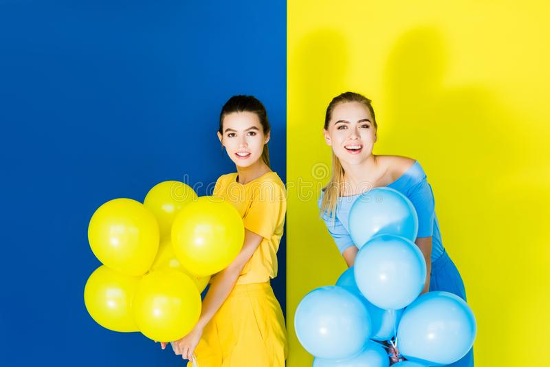 Elegant stylish women smiling and holding party balloons on blue. And yellow background stock image
