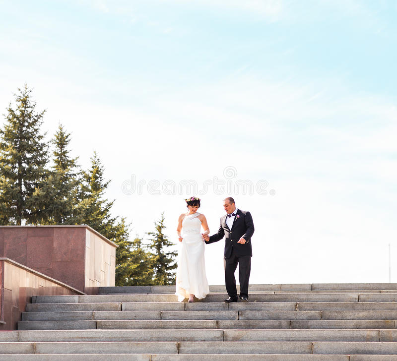 Elegant stylish young couple beautiful bride and groom on the stairs. royalty free stock images