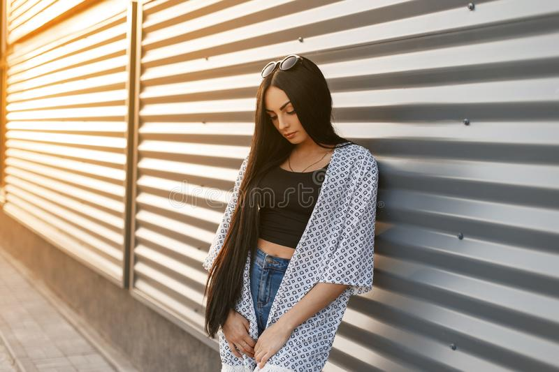Elegant stylish young woman with luxurious black hair in a stylish cape in a fashionable t-shirt in vintage blue jeans posing. Near a modern metal wall at stock photos