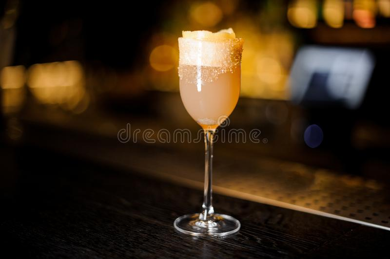 Elegant sweet wine glass filled with delicious brandy crusta cocktail on the bar counter royalty free stock images