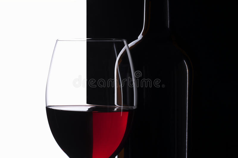 Elegant symmetry red wine glass and a wine bottle. In black and white background stock images