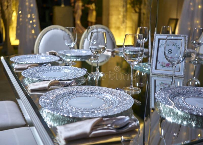 Elegant tabellinställning, lyxiga plattor för matställen, elegant balsal för bröllopmottagandet, garneringidéer, blommahöjdpunkt royaltyfri foto