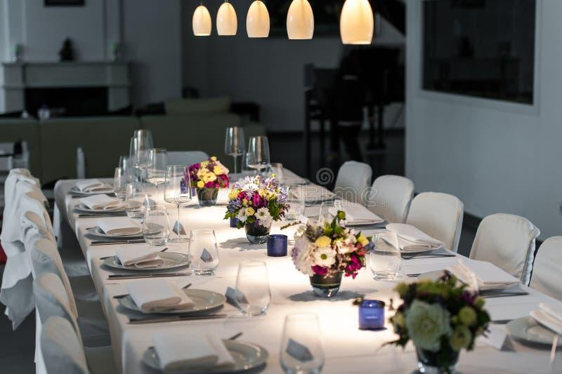 Elegant tabellinställning med ljusa fläckar och blommor arkivfoto