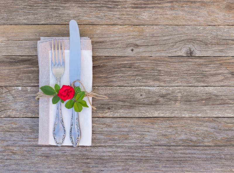 Romantic dinner concept, table setting with cutlery and red rose flower on wooden background stock image