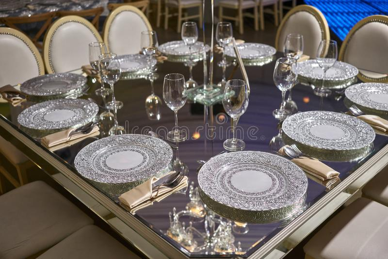 Elegant table setting, luxury cristal plates for dinner, elegant ballroom for night wedding reception, flowers centerpiece. Luxurious romantic party table royalty free stock images