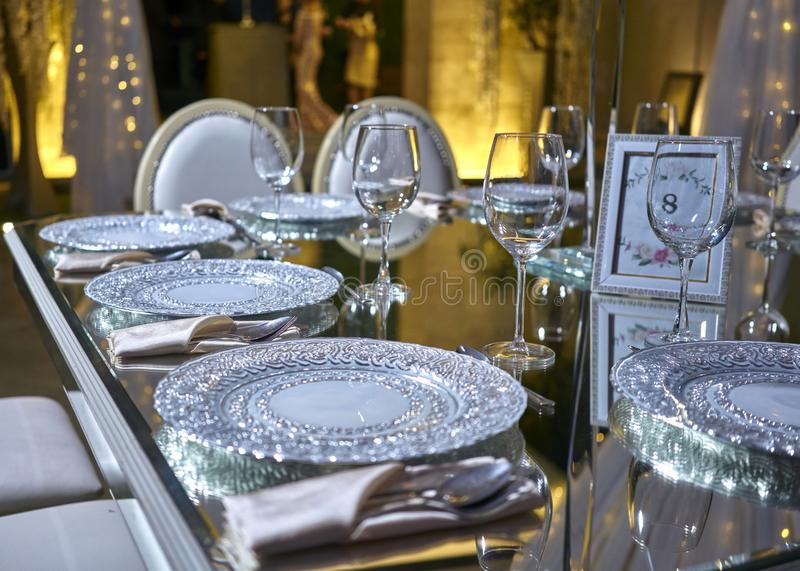 Elegant table setting, luxury plates for dinner, elegant ballroom for wedding reception, decoration ideas, flowers centerpiece. Luxurious romantic party table royalty free stock photo
