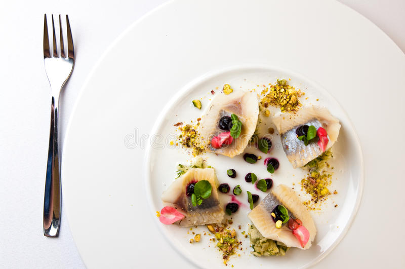 Elegant table setting with herring fish. Elegant table setting in a restaurant. Food photography of herring fish pieces served on white plate stock photos
